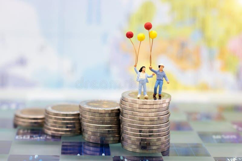 Miniatuurmensen: De gelukkige kinderen koppelen status op muntstukkenstapel stock afbeelding