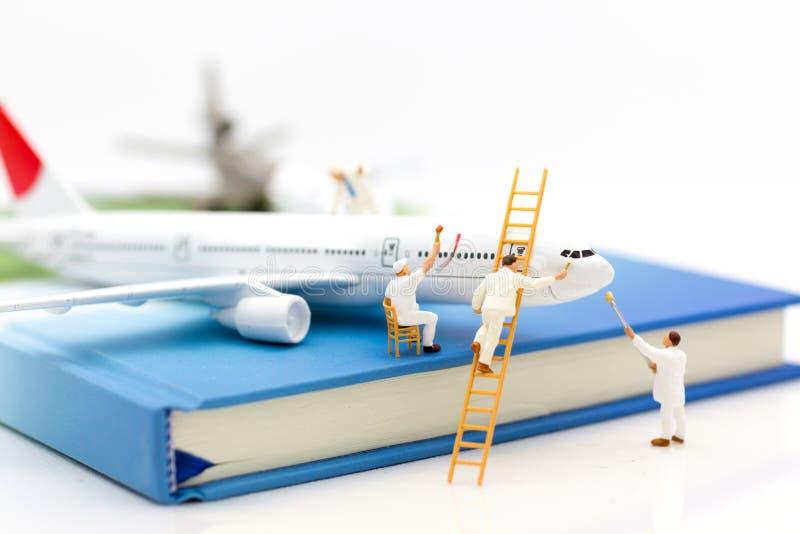 Miniatuurmensen: De groepsarbeider herstelt het vliegtuig Beeldgebruik voor onderhoud, Verbetering, bedrijfsconcept stock foto
