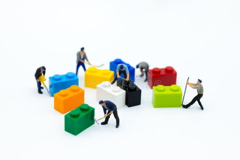 Miniatuurmensen: De hulpmiddelen van het arbeidersgebruik met de kleurrijke dozen voor reparatie Beeldgebruik voor achtergrondzak royalty-vrije stock foto