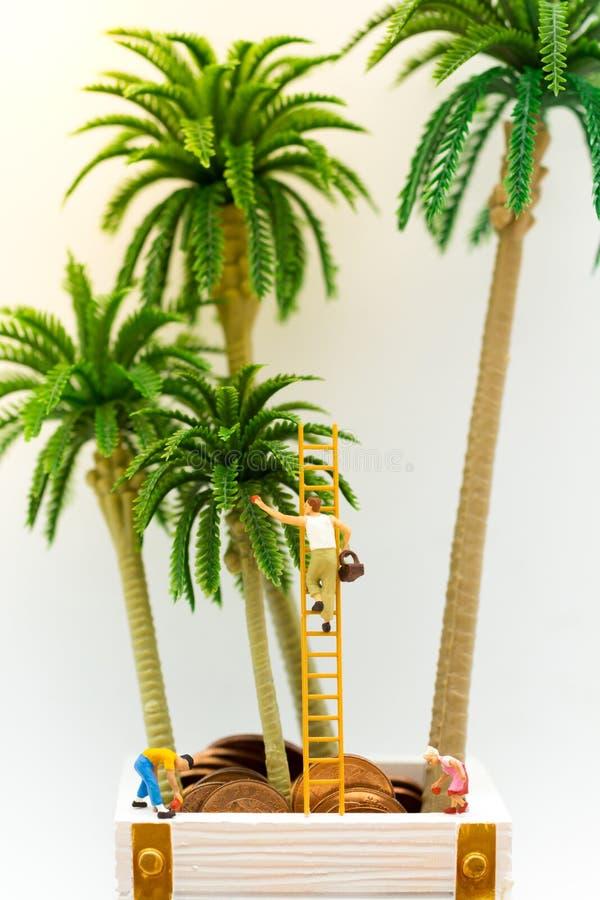 Miniatuurmensen: De kerel beklimt de ladder om fruit van de boom te verzamelen en de kinderen houden hieronder vruchten Beeldgebr stock fotografie