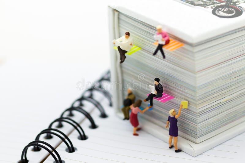 Miniatuurmensen: de krant van de zakenmanlezing op een groot boek Beeldgebruik voor achtergrondonderwijs of bedrijfsconcept royalty-vrije stock foto