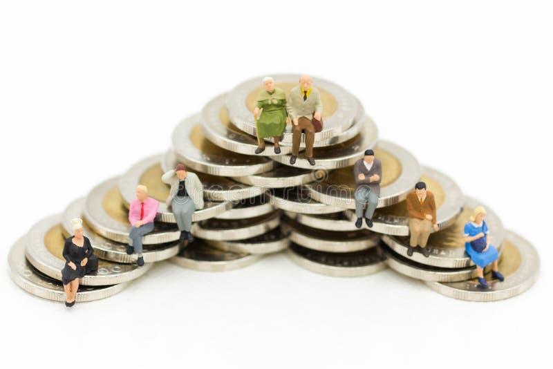 Miniatuurmensen, de Oude zitting van het paarcijfer bovenop stapelmuntstukken die als achtergrondpensionering planning gebruiken, stock foto