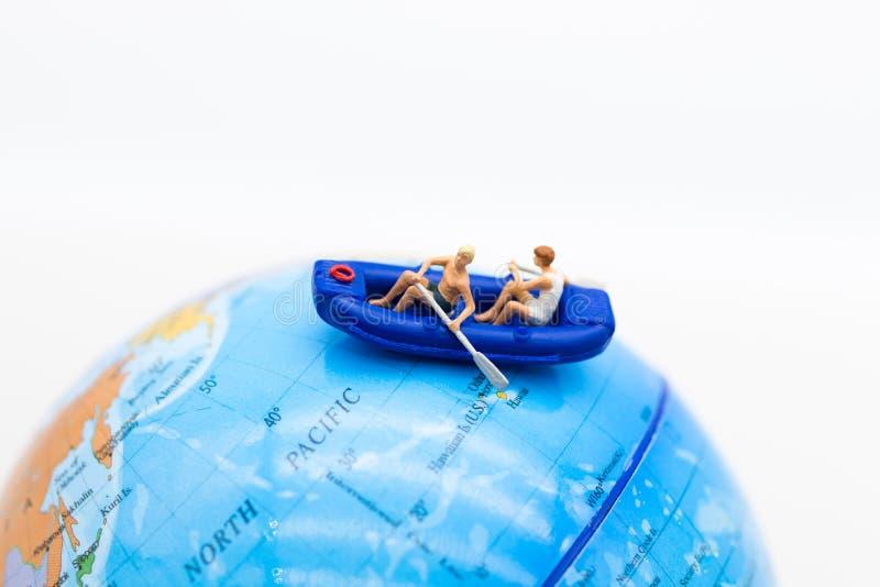 Miniatuurmensen: De reizigers met peddelboot op wereld brengen in kaart Beeldgebruik voor activiteiten, reis bedrijfsconcept stock foto's