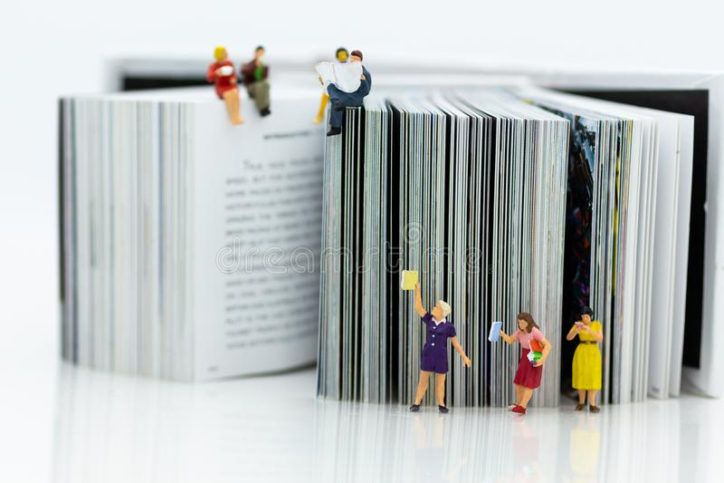 Miniatuurmensen: De studenten gelezen boeken, houden boeken op boekenrekken Beeldgebruik voor onderwijsconcept royalty-vrije stock afbeeldingen