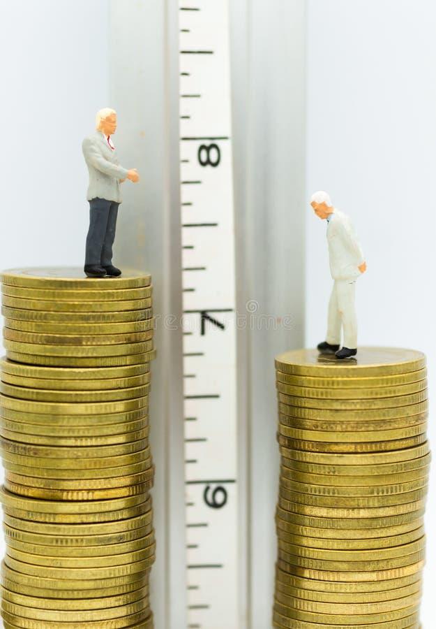 Miniatuurmensen: De zakenlieden bevinden zich op stapel muntstukken, hoog en laag Beeldgebruik voor bedrijfs de concurrentieconce stock fotografie