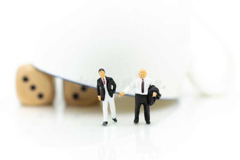 Miniatuurmensen: De zakenman met een glas met dobbelt binnen, risicodragende investering Beeldgebruik voor bedrijfsconcept royalty-vrije stock afbeeldingen