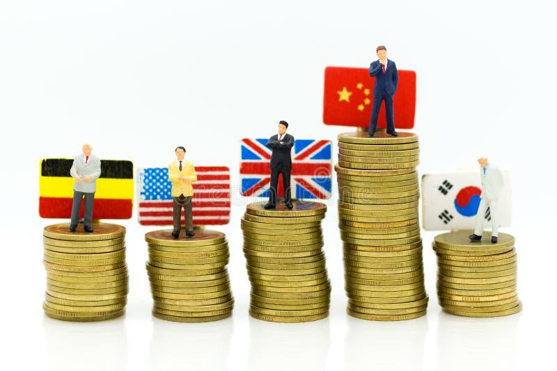 Miniatuurmensen: De zakenmantribune op stapelmuntstukken met de vlag van het land, toont de winsten van marketing in elk land stock fotografie
