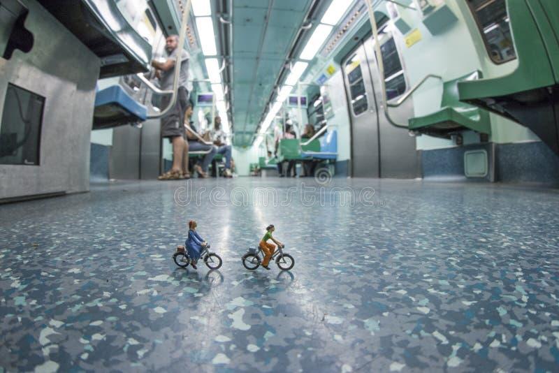 Miniatuurmensen die fietsen in metro berijden stock afbeelding