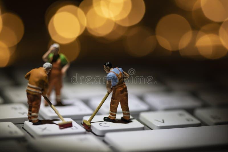 Miniatuurmensen die witte toetsenbordcomputer schoonmaken royalty-vrije stock afbeelding