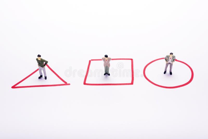 Miniatuurmensen drie bedrijfsmensen die zich in rode diagrammen bevinden ove royalty-vrije stock afbeelding