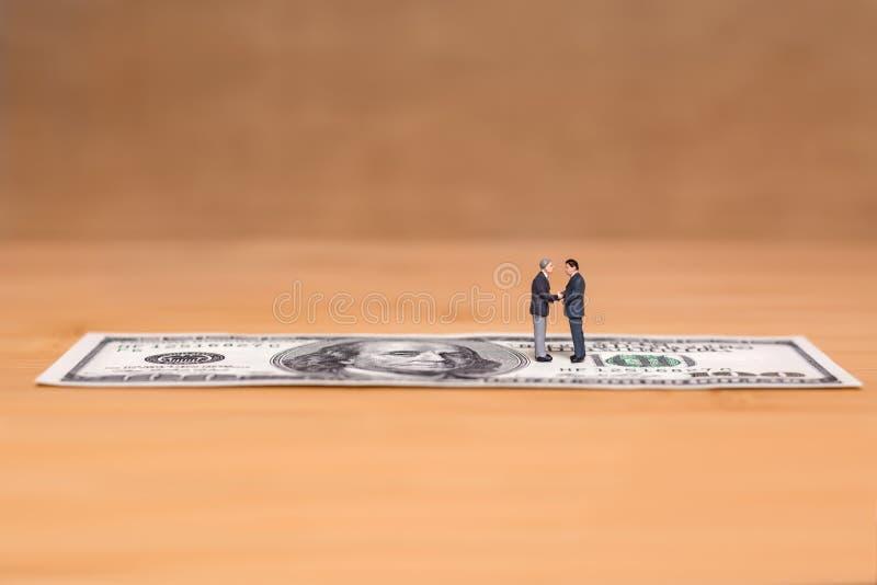 Miniatuurmensen en geld Creatief concept een overeenkomst De handen van de Businessmensschok royalty-vrije stock afbeelding