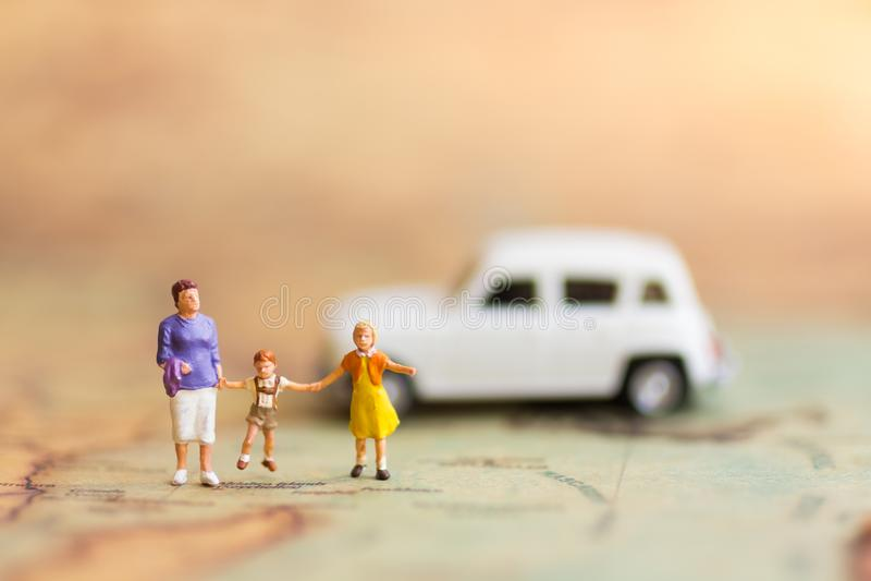 Miniatuurmensen, familie die zich op de reis van het kaartwoord aan de bestemming met de auto bevinden, die als familieconcept ge royalty-vrije stock afbeeldingen