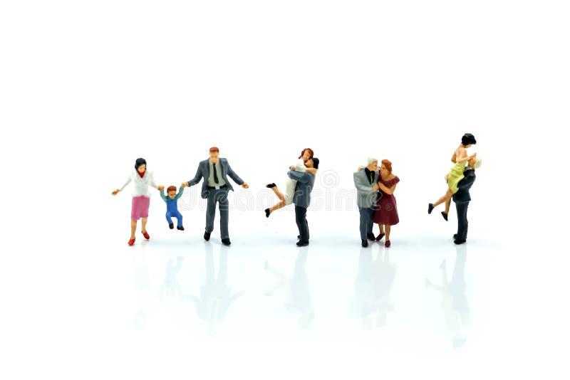 Miniatuurmensen: Familie en gelukkig paar die van liefde voelen stock foto