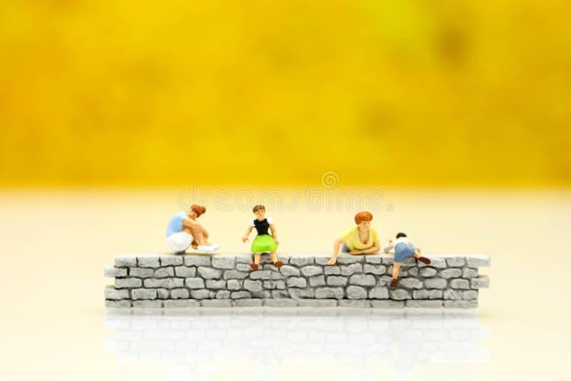 Miniatuurmensen: Familie en kinderen het zitten van muur met hous stock foto's