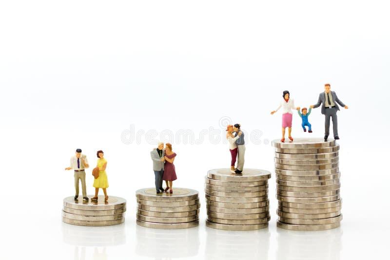 Miniatuurmensen: Het cijferzitting van het groepspaar bovenop stapelmuntstukken Beeldgebruik voor pensionering planning, levensve royalty-vrije stock afbeelding