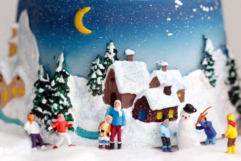 Miniatuurmensen: kinderen die pret met sneeuwman spelen Concept van royalty-vrije stock afbeelding