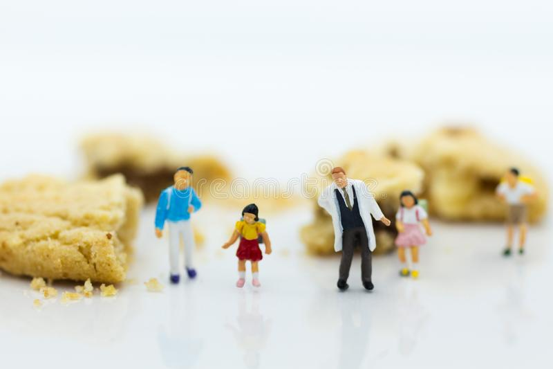Miniatuurmensen: Kinderen en artsen die zich naast koekjes bevinden Het beeldgebruik voor waarschuwingskinderen niet teveel snoep stock fotografie