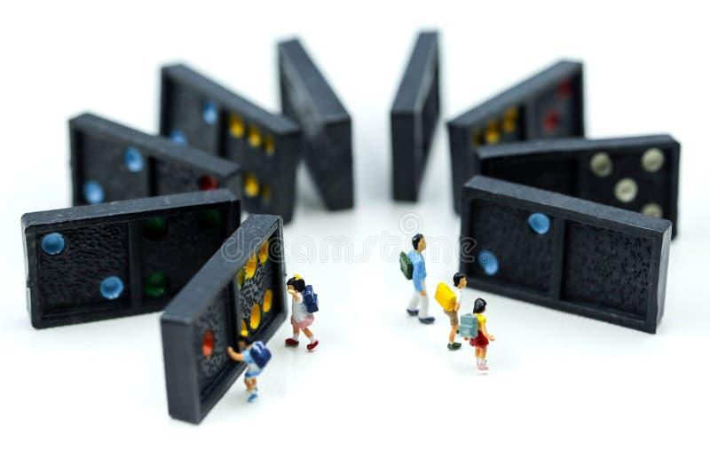 Miniatuurmensen: kinderen en student met Domino, die spelen en stock afbeeldingen