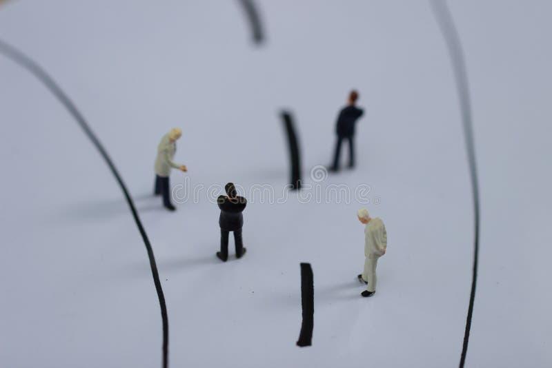 Miniatuurmensen: Kleine zakenmancijfers die op de straat lopen stock fotografie