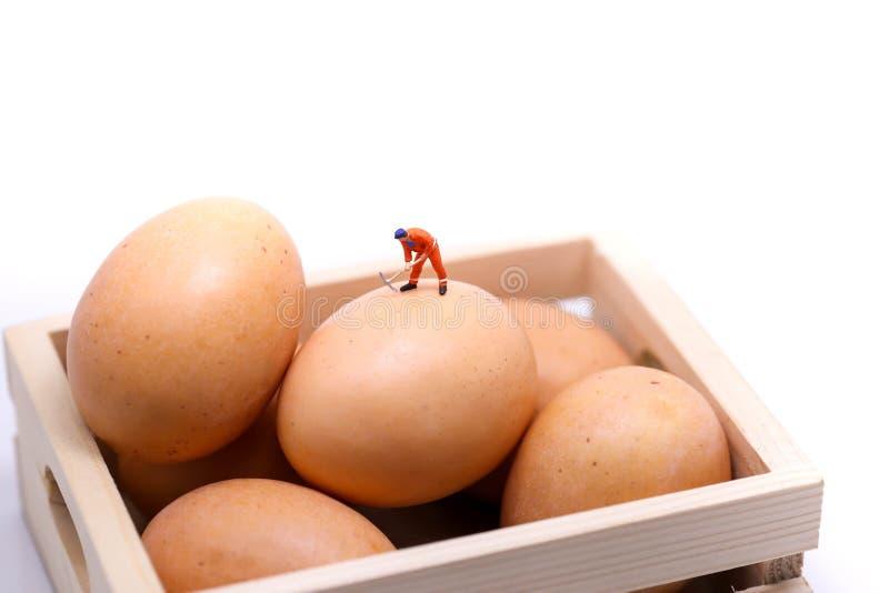 Miniatuurmensen: mens die aan eieren, idee of Pasen-dagconce werken stock fotografie