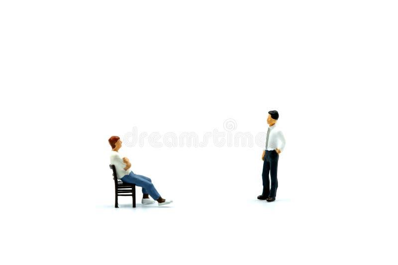 Miniatuurmensen: Mens die een stoel met zakenman zitten royalty-vrije stock afbeeldingen