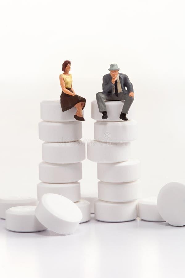 Miniatuurmensen - mensen die voor pillen stellen stock afbeelding