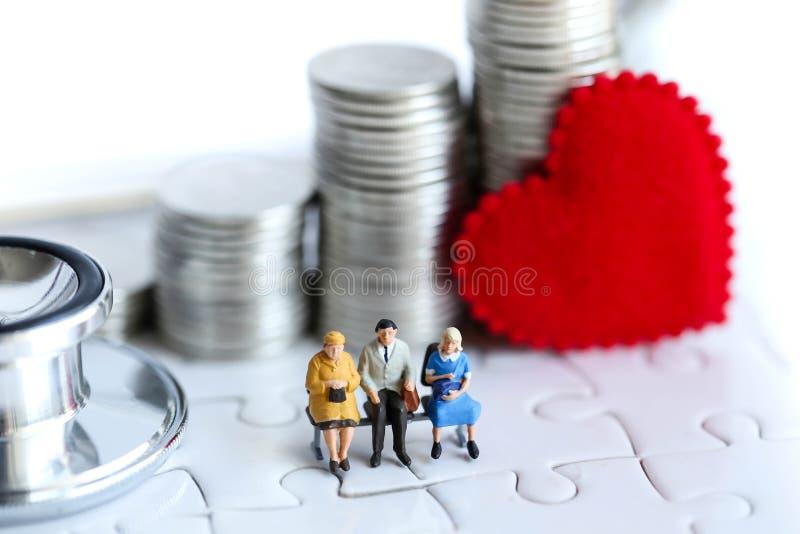 Miniatuurmensen: oldman zitting met het hart van stapelmuntstukken en ste stock afbeeldingen