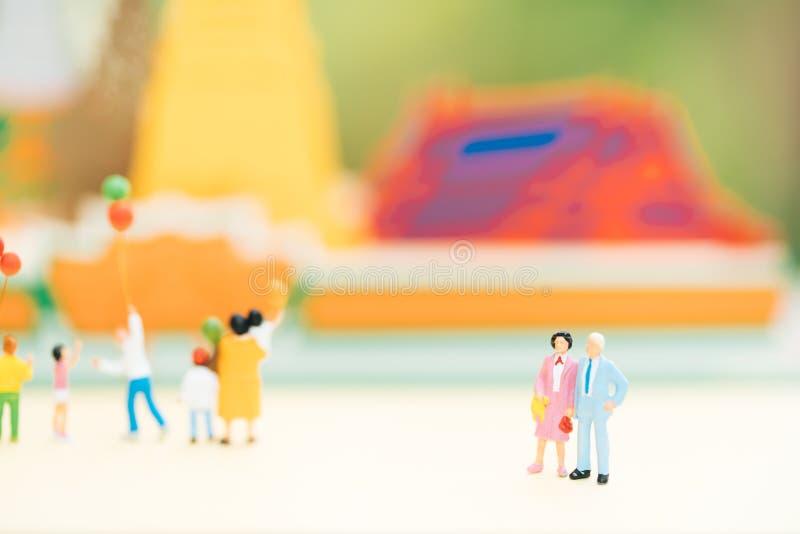 Miniatuurmensen: Oud paarcijfer die zich voor tempel met anderen toerist bevinden stock afbeelding