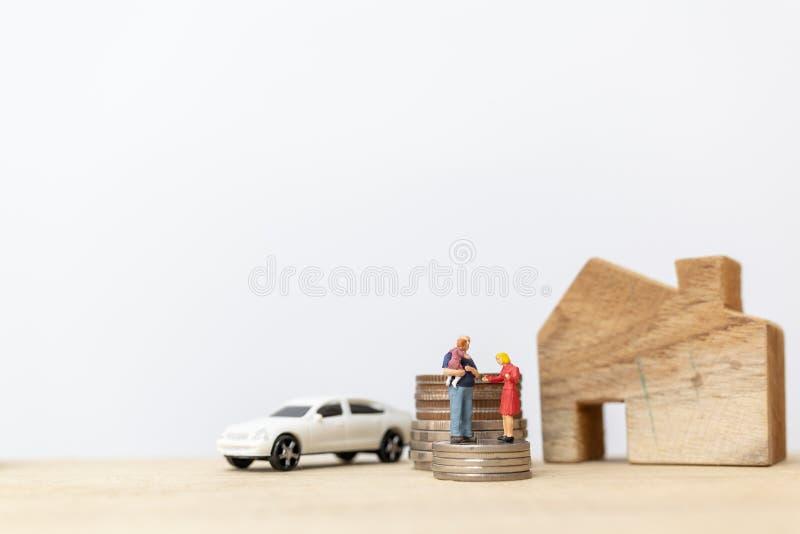 Miniatuurmensen: Ouders met kinderen met huis en Muntstukken het Stapelen stock foto