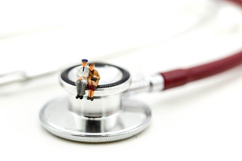Miniatuurmensen: Paar van oldman zitting met medische stethos royalty-vrije stock foto's