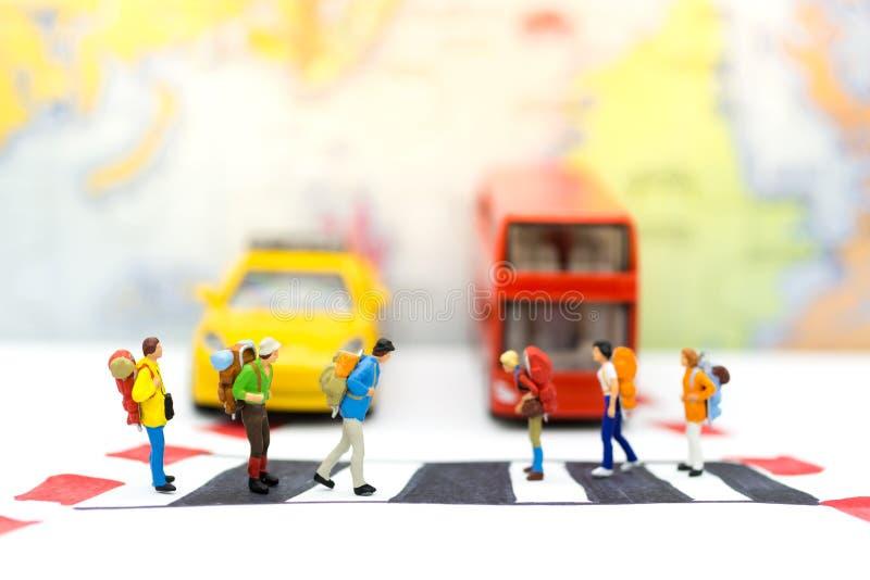 Miniatuurmensen: Reizigerszebrapad de straat op de stadsstraten Beeldgebruik voor eerbied voor verkeersregels, reisconcept royalty-vrije stock foto's
