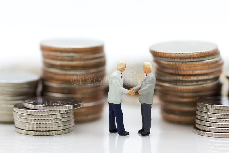 Miniatuurmensen: Twee zakenlieden maken tot een overeenkomst, met stapel muntstukken aan achtergrond, gebruikend als verplichting royalty-vrije stock afbeelding