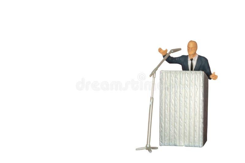 Miniatuurmensen van een politicus die met microfoon spreken isolat royalty-vrije stock afbeeldingen