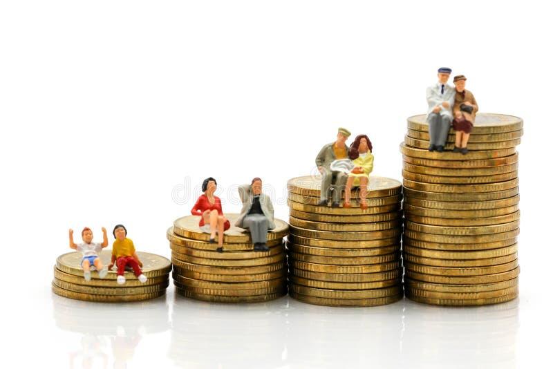 Miniatuurmensen: Veelvoudige leeftijdszitting op stapel muntstukken, zaken stock afbeelding