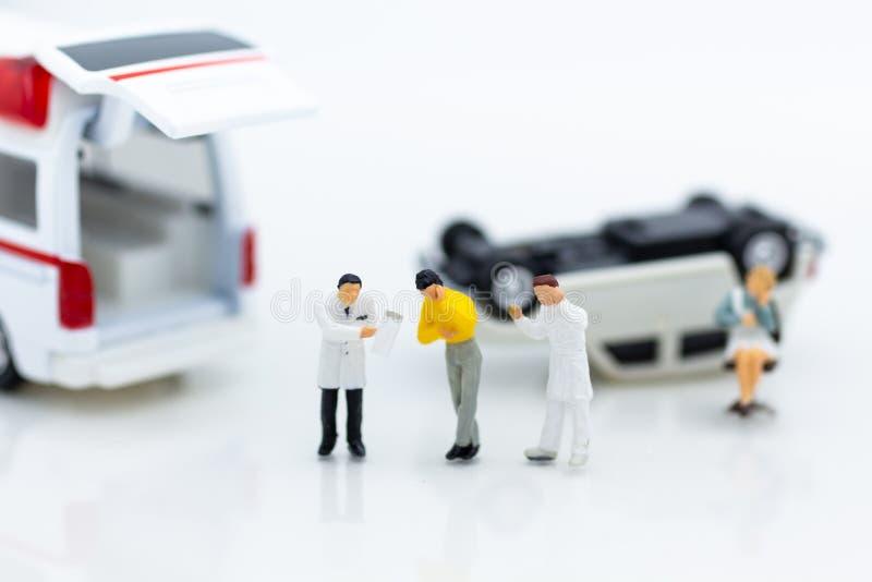 Miniatuurmensen: Verwonde die persoonlijk van verkeersongevallen, ziekenwagen aan het ziekenhuis voor behandeling wordt vervoerd stock foto