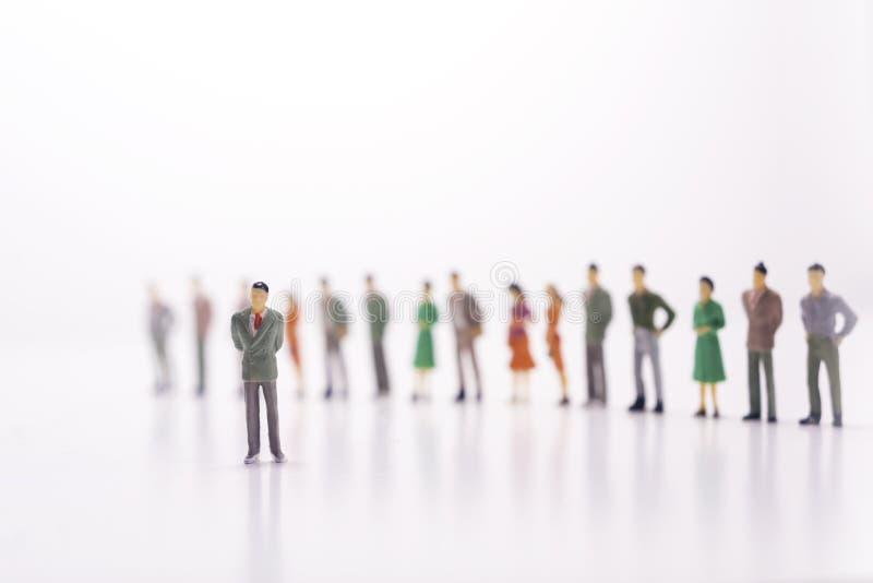 Miniatuurmensen, werkgever tegen de lijn van mensen over wit stock foto's