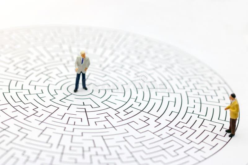 Miniatuurmensen: Zakenman die zich op centrum van labyrint bevinden stock foto's