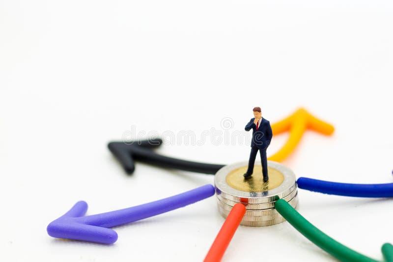 Miniatuurmensen: Zakenman die zich voor de keus van de pijlweg bevinden Beeldgebruik voor economisch besluitconcept royalty-vrije stock afbeelding