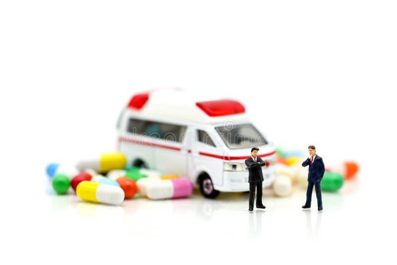 Miniatuurmensen: Zakenman met Ziekenwagen en capsuledrug, B stock afbeelding