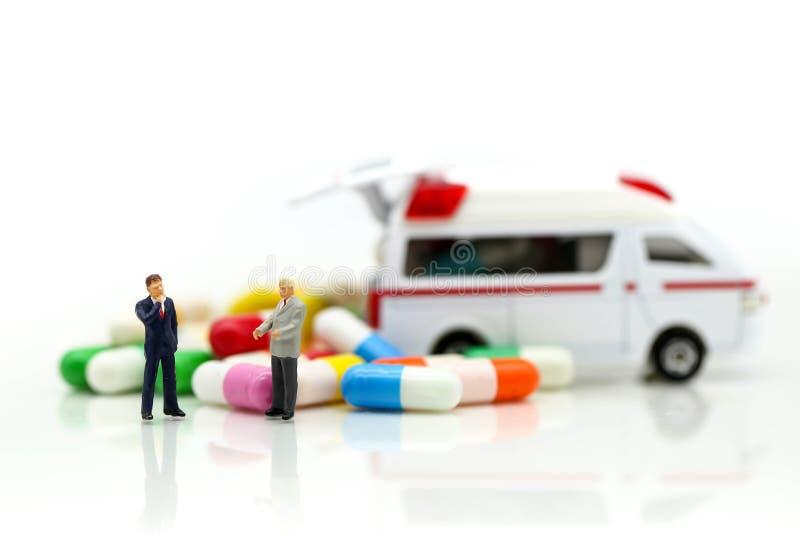 Miniatuurmensen: Zakenman met Ziekenwagen en capsuledrug, B stock afbeeldingen