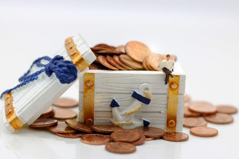 Miniatuurmensen: Zakenmanzitting op blok met muntstukken Busin royalty-vrije stock foto's