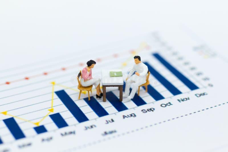 Miniatuurmensen: Zakenmanzitting op stoel en vergaderings bedrijfsgrafieken, winstmarges van achtergrond Beeldgebruik voor zaken royalty-vrije stock afbeeldingen