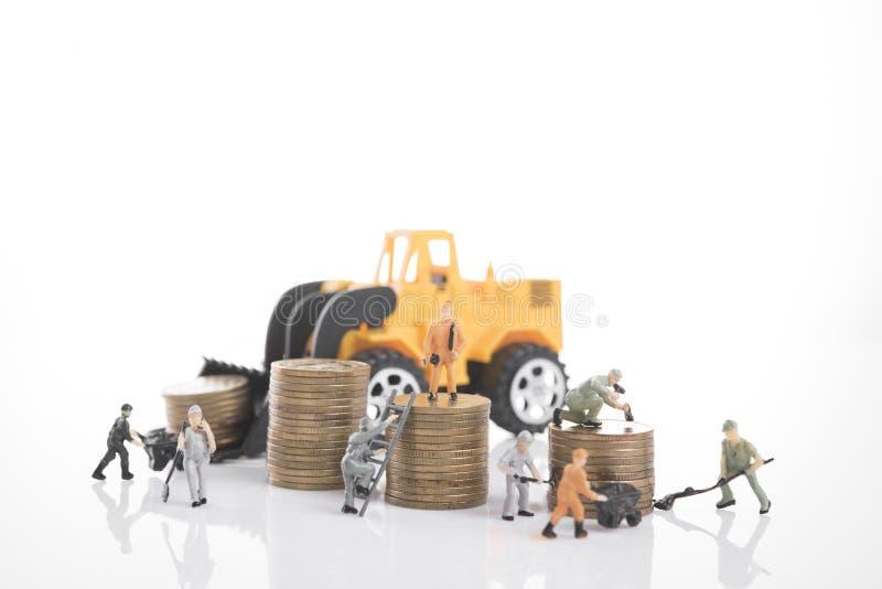 Miniatuurmensenarbeiders op de stapels van het geldmuntstuk bedrijfsinvesment stock afbeelding