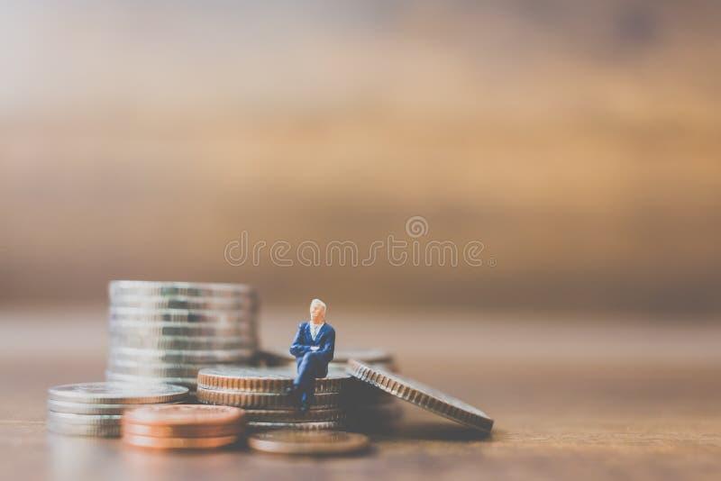 Miniatuurmensenzakenman op muntstukken royalty-vrije stock fotografie