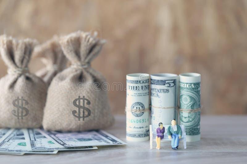 Miniatuurpaar die zich op de stoel en geldzak met bankno bevinden royalty-vrije stock afbeeldingen