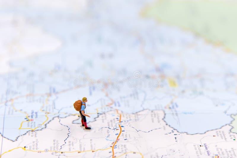 Miniatuurreiziger met rugzak die zich op woldkaart voor reis rond de wereld bevinden stock fotografie