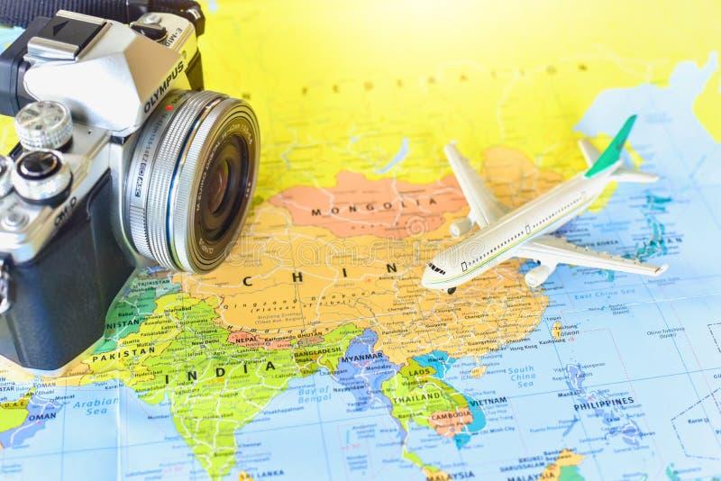 Miniatuurvliegtuig en Uitstekende Mirrorless-Camera op de Achtergrond van de Wereldkaart stock afbeeldingen