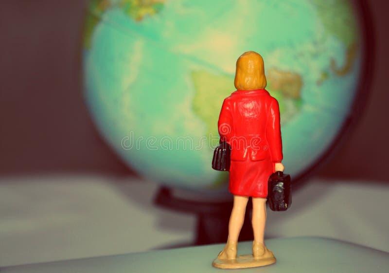 Miniatuurvrouw die de bol bekijken Het minicijfer van erachter met een bol om kaartmodel, reist globaal concept royalty-vrije stock fotografie