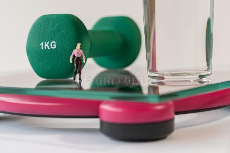 Miniatuurvrouwencijfer die zich op de digitale elektronische badkamersschaal bevinden voor gewicht van menselijk lichaam Glas wat royalty-vrije stock foto's