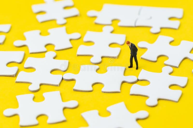 Miniatuurzakenman in kostuum die en op witte puzzel op stevige gele achtergrondmetafooroplossing aan het oplossen kijken denken stock afbeeldingen